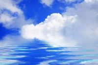 White clouds and blue sky on a sunny day with water reflection