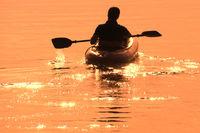 Mann paddelt mit Schlauchboot in den Sonnenuntergang