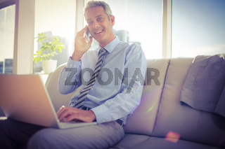 Businessman sitting on a couch having phone call and using laptop