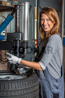 Female mechanic changing car tire.