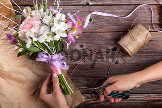 Preparing a rustic bouquet from gillyflowers and alstroemeria on old wooden background with wooden heart and scissors with paper