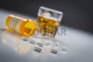 Prescription Drugs Spilled From Fallen Bottle Near Glass of Alcohol