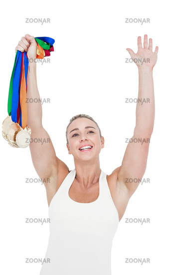 Happy female athlete holding medals