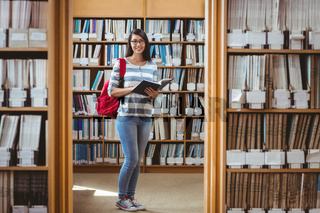 Pretty student with backpack reading a book in library