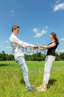 Young attractive couple holding each other in sunny meadow