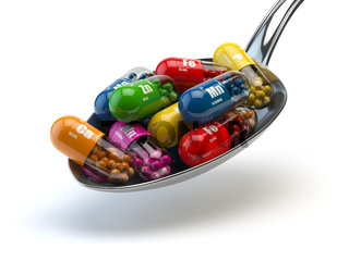 Capsules and pills on the spoon, isolated on white. Dietary supplements.