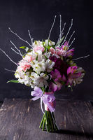 Pink bouquet from gillyflowers and alstroemeria on blackboard and old wood