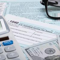 US 1040 Tax Form, calculator, glasses and dollars - studio shot