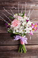 Rustic bouquet from gillyflowers and white alstroemeria on old, rustic wooden background