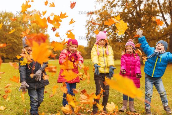 happy children playing with autumn leaves in park