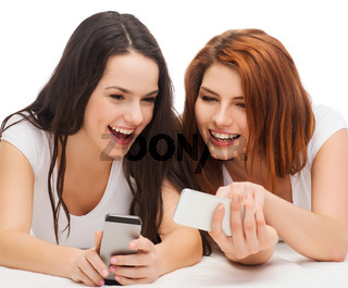 two smiling teenagers with smartphones