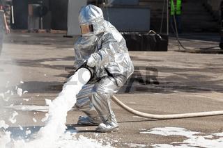 Firemen spray firefighting foam
