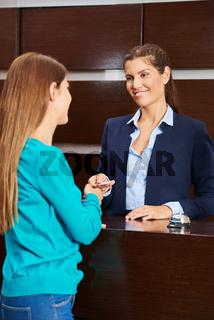 Empfangsdame gibt Frau den Zimmerschlüssel