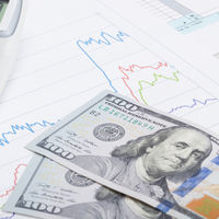 Stock market graph with calculator and 100 dollars banknote - studio shot