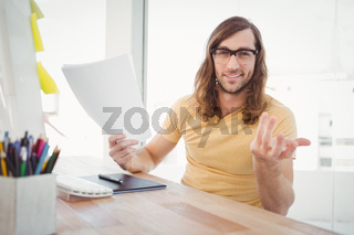 Portrait of happy hipster gesturing in office