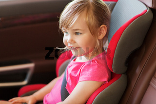 happy little girl sitting in baby car seat