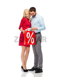 happy couple looking into red shopping bag