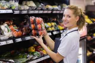 Portrait of a smiling blonde worker taking a tomatoes