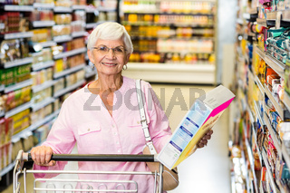 Smiling senior woman holding corn flakes box