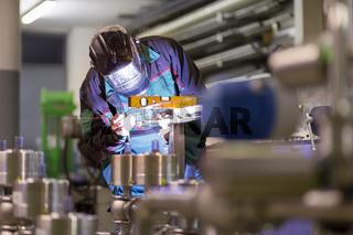 Industrial worker welding in metal factory.