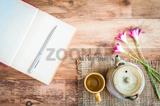 Tea cups with teapot with open book on old wooden table. Top view.