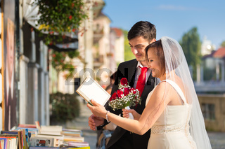 Beautiful wedding couple reviewing vintage books.