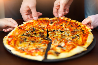Big family hands taking pizza from plate