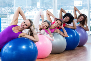 Smiling women stretching on exercise balls with hands behind head