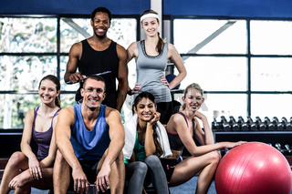 Smiling fitness class posing together