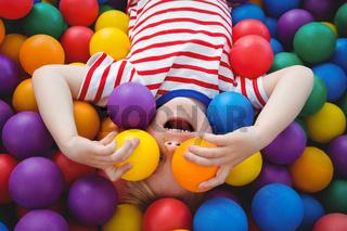 Cute smiling boy in sponge ball pool