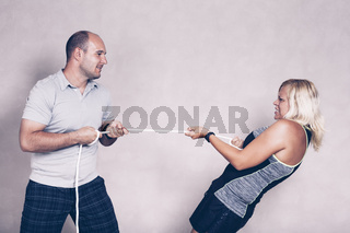 Sporty determined woman and man pulling a rope