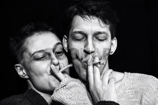 Young man and woman smoking cigarettes