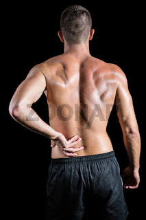 Shirtless athlete with back pain