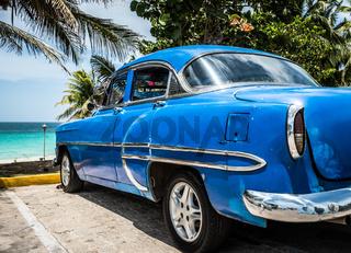 Blauer amerikanischer Oldtimer parkt am Strand in Kuba