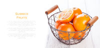 Fresh juicy summer blood oranges in a vintage basket with mint leaf on wooden table on a white background with copy space
