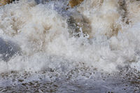 Sea wave bubbles and splashes closeup view
