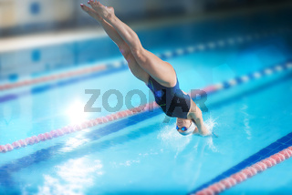 Female swimmer, that jumping into indoor swimming pool.