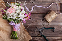 Rustic bouquet from gillyflowers and alstroemeria on old wooden background with wooden heart and scissors with paper