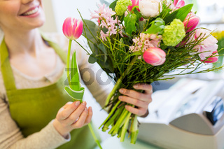 close up of woman making bunch at flower shop
