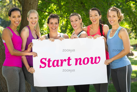 Start now against fitness group holding poster in park