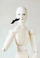 Wooden puppet with fake mustache