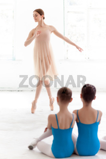 Two little ballerinas dancing with personal ballet teacher in dance studio