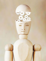Many cogwheels working into the human head. Abstract image with wooden puppet