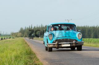 Blauer amerikanischer Oldtimer fährt auf der Landstrasse im Landesinneren von Kuba