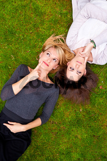 Two girls lying in the grass