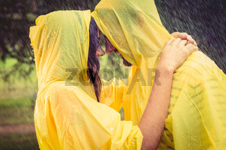Cute couple wearing protection cape and hugging under the rain