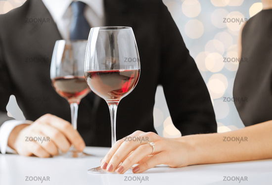 hands of couple with diamond ring and wine glasses