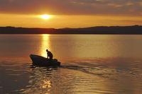 Fischer mit Motorboot bei der Ausfahrt im Sonnenaufgang