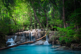 Jangle landscape with flowing turquoise water of Erawan cascade waterfall at deep tropical rain forest. National Park Kanchanaburi