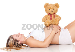Pregnant woman with a cute teddy bear sitting on her belly